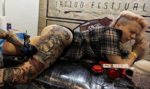 A client reacts as she is tattooed during the Tattoo Week SP 2016 in Sao Paulo
