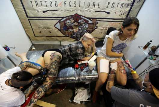 Tattoo artists work on clients during the Tattoo Week SP 2016 in Sao Paulo