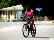 Jovem conduzindo uma bicicleta na principal artéria da Vila de Palma, norte de Moçambique/Foto: Edmundo Galiza Matos
